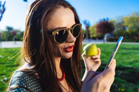 Young beautiful girl in sunglasses sits on the lawn with bright green grass, correspond with someone on the phone Stock Photo