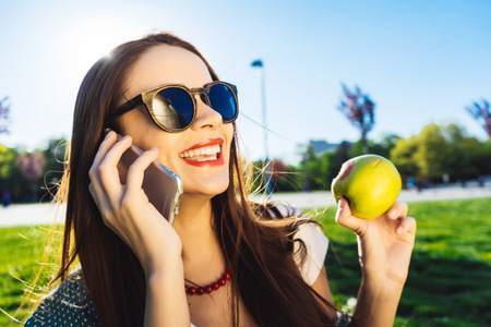 Cheerful young girl with long hair sitting on lawn in park, eating green apple, talking on phone Stock Photo