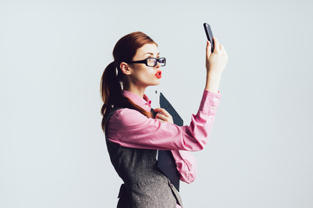 Young woman teacher with red hair in glasses holds a phone in her hand, lifted the phone upwards Stock Photo
