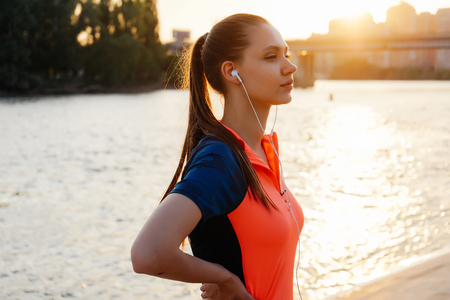 Young athletic woman stops on a jog, listens to music on headphones, against the background of a river park and city