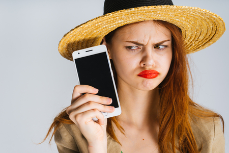 Angry young businesswoman in stress looks at a black smartphone screen