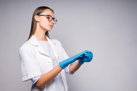 Jonge serieuze vrouwelijke arts legt handschoenen aan voor de operatie. Laboratorium Stockfoto