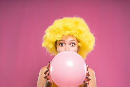 A surprised girl clown in a wig inflates a ball to her birthday. Bubble of pink chewing gum