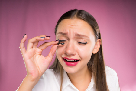 A young woman removes  pastes artificial eyelashes. Eyelash extension, frightened face Imagens