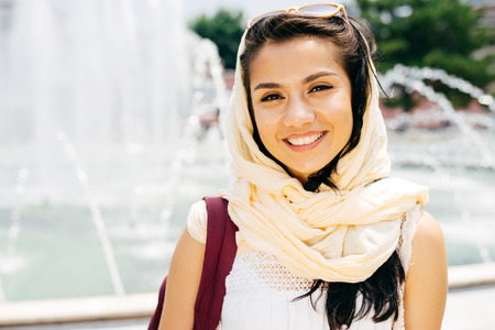 Modern Muslim woman in scarf and glasses smiles