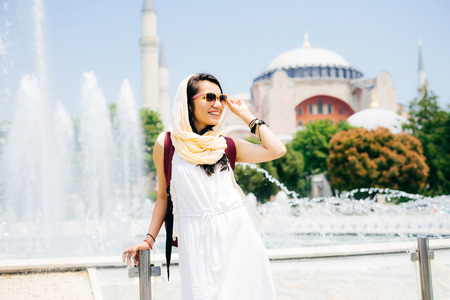 Fashion portrait of a young modern Muslim woman on summer vacations in glasses, looks into the distance, a mosque on the background. Summer trip, vacation
