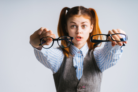 perturbed: funny red-haired girl with two tails holds in her hands two pairs of glasses Stock Photo