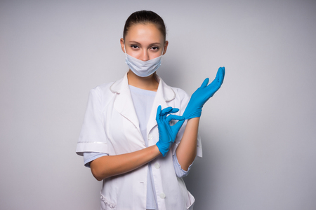 A strict woman doctor puts on gloves and looks into the camera, getting ready