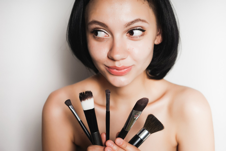 a smiling girl chooses what cosmetics to take advantage of