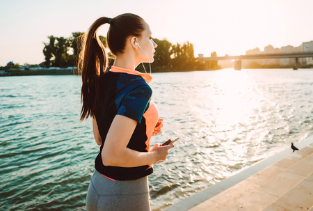sporty girl in headphones doing an evening run at sunset by the river with a phone in hands