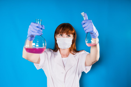 a girl in medical uniform holds flasks with medical preparations