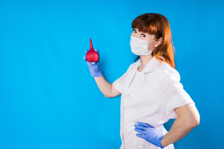 a nurse in a mask holds a medical pear in his hands and looks into the camera Stock Photo