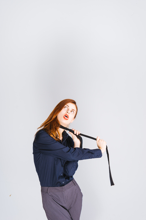 Tired woman in a suit tries to hang herself, strangle herself with a tie. Tired of working, stress