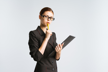 a girl in glasses and a strict suit carefully examines the documents