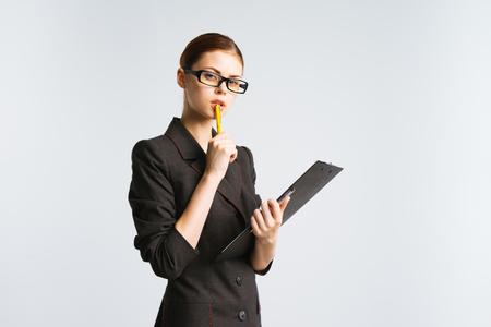 Una chica en gafas y un traje estricto cuidadosamente examina los documentos Foto de archivo - 87347560