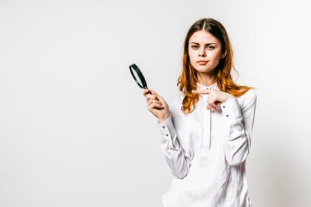 Belle fille rousse dans une longue chemise blanche tient une loupe et regarde la caméra Banque d'images - 87347606