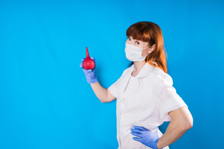 a girl in medical clothes and a mask holds a medical pear in her hands and looks into the camera, isolated on a blue background