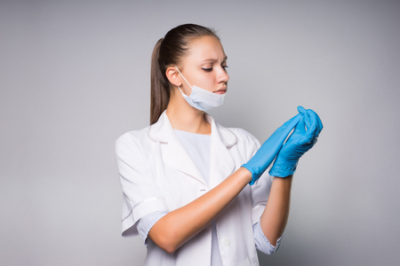 girl nurse in gloves examines something carefully at the tips of her fingers Stock Photo