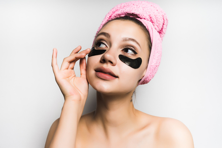 girl with a towel tied around her head puts a black mask on her face
