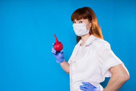 woman doctor prepares syringe in medical mask Stock Photo