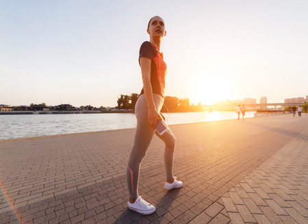 a young girl with a phone in her hands stopped during the evening jogging Stock Photo