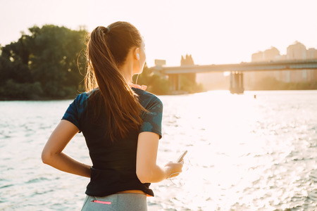 a girl in a sportive uniform performs an evening run with a phone in her hands