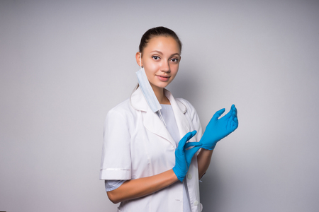 lovely lady in medical clothes looks at the camera, isolated