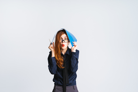 perturbed: surprised red-haired girl with glasses holds a blue folder with documents on her head Stock Photo