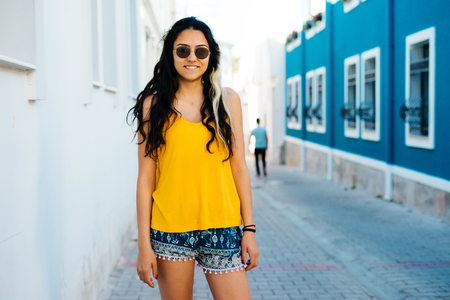 voyage: Woman traveler on the street,bright t-shirt,sun glasses