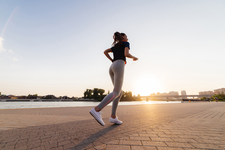 the girl in sports uniform performs an evening run at sunset