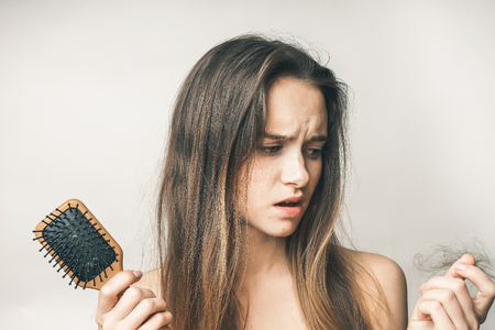 the girl with a comb in hands with the stunned expression is upset because of a torn scrap of hair