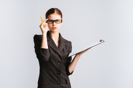 attentive business lady in a black suit is holding a folder and a pen, holding her glasses and looking directly at the camera Stock Photo