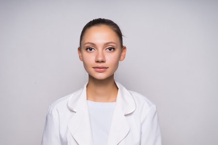 a serious girl with a small smile in her white coat is standing straight and looking straight into the camera Stock Photo