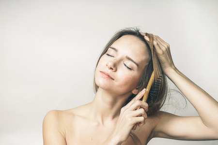 woman brushing her hair with enjoy closed eyes