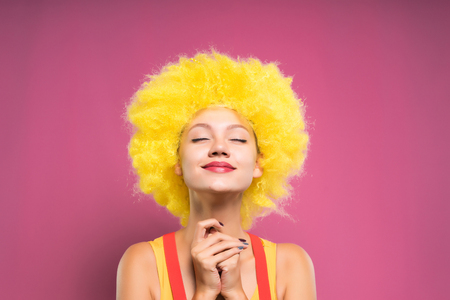 funny girl in yellow wig smiling with closed eyes