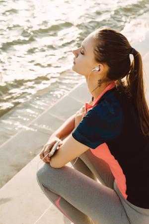 La jeune fille en uniforme de sport avec le téléphone dans ses mains se pencha sur les marches par la rivière Banque d'images - 87803738