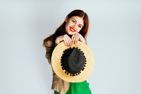 red straw: smiling girl with hat in hands on a white background