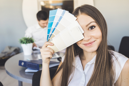 cute smiling girl in the office chooses a color from the palette Stock Photo
