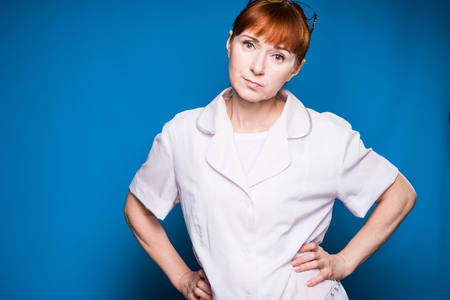 girl in medical clothes strictly looks at the camera, isolated on a blue background