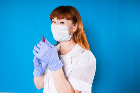 woman doctor in a medical mask smiling holding a pen Stock Photo