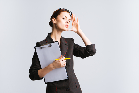 serious beautiful girl in a black suit holds in her hands a folder with sheets a4 Stock Photo