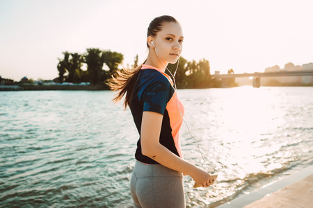 sporty girl walks by the river at sunset Stock Photo