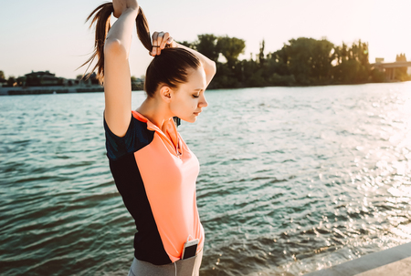 girl in a sporty uniform stands against the background of the river adjusting her pigtail