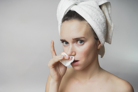 Woman removes cosmetics with cotton swab, cleaning face Stock Photo