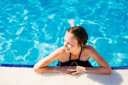 Retreat and vacation.Beautiful young woman relaxing in spa swimming pool.
