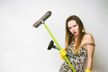 Woman cleaner with passion, the girl prepares to do the cleaning, holds the mop in her hands and looks directly into the camera Stock Photo