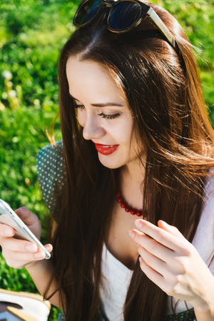Woman looking something in mobile,texting,addicted, green lawn Stock Photo