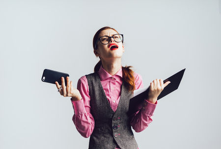 telephone interview: business young girl holding a folder and phone and looks disappointed and angry
