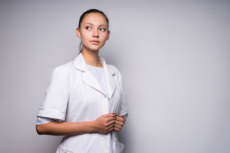 a girl in a white medical dressing gown looks curiously toward