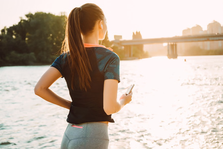 the girl is engaged in sports in headphones by the river